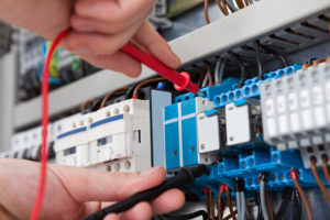 , close up of an electricians hands carrying out an electrical test with probes